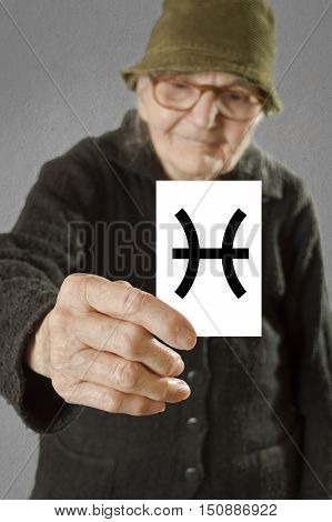 Elderly woman holding card with printed horoscope Pisces sign. Selective focus on card and fingers.