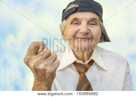 Elderly woman showing fig sign. Selective focus on hand