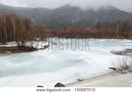 Icebound River On A Cloudy Spring Day. Irkutsk Region