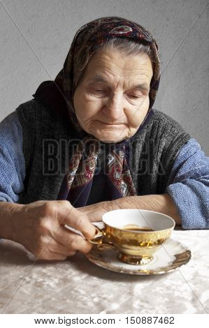 Portrait of an elderly woman drinking coffee on a vintage background. Dreaming the past
