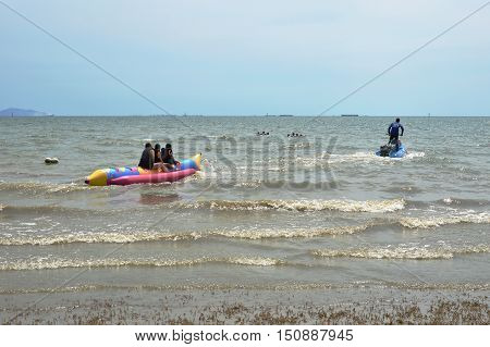 Chonburi Thailand April 5, 2014 jet ski dragging banana boat with traveler from beach to the sea
