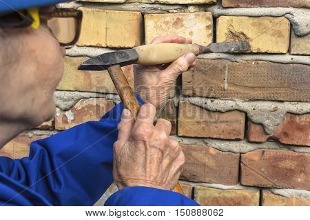 Elderly woman holding a hammer and chisel selective focus.