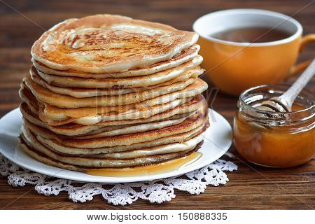 Stack of delicious, homemade pancakes with honey on white plate on wooden background. Healthy breakfast, close up. Pancake's Day. High stack of pancakes shallow DOF.