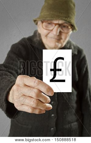 Elderly woman holding card with printed english pound sterling mark. Selective focus on card and fingers.