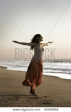Beautiful woman with open arms felling the wind