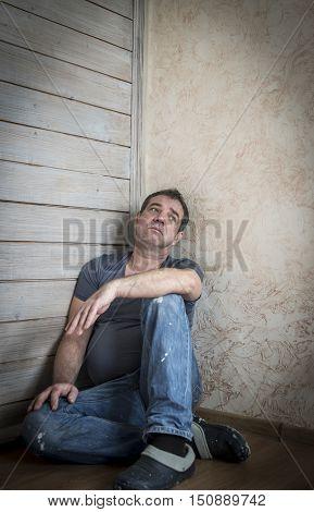 Portrait of a sad man sitting against the wall