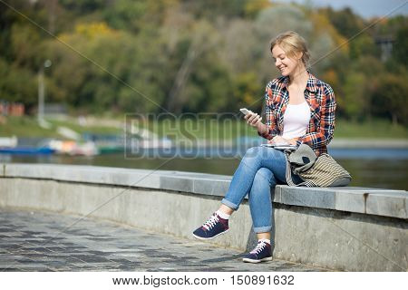 Portrait of a young attractive girl sitting her legs crossed at the bridge, waterline behind, looking at the screen of her mobile, lifestyle