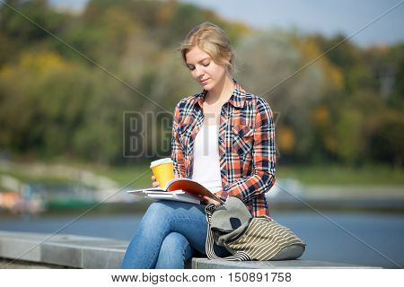 Portrait of a young attractive student girl sitting her legs crossed, at the bridge, reading, coffee at her hand waterline behind, back to school concept photo, lifestyle, horizontal
