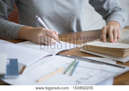 Student female hands performing a written task in a copybook with a pen, education concept photo. Close up