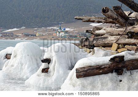 Iced Old Ruined Wooden Pier With Large Goloustnoye Village St. Nicholas Church On Background. Baikal