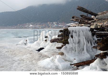 Iced Old Ruined Wooden Pier With Large Goloustnoye Village On Background. Baikal Lake