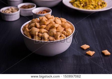 homemade tasty Diwali food or Diwali snacks or Diwali sweets like rava laddu, chakli, sev, shankar pale and chivda or chiwada with dry fruits in white bowls, favourite indian diwali recipe