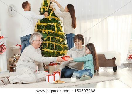 Grandparents giving Christmas present to their granddaughter