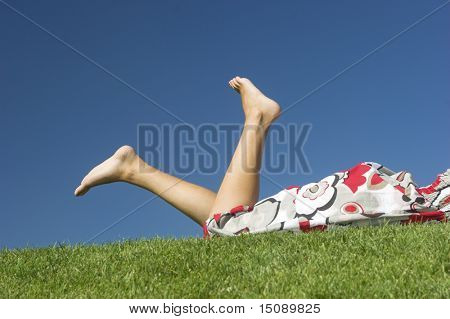 Picture of woman legs in a beautiful green field