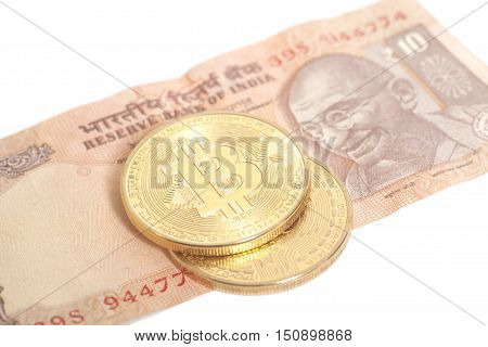 Golden bitcoin coins on Indian Ten Rupee isolated on white