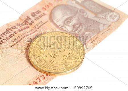 Golden bitcoin coin on Indian Ten Rupee isolated on white
