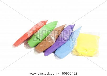Colored polymer clay in packages isolated on white
