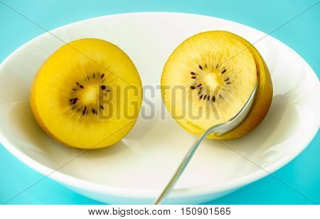Two Golden Kiwi halves in a white porcelain bowl on aqua blue background. A spoon for scooping out the flesh in one half of the kiwis.