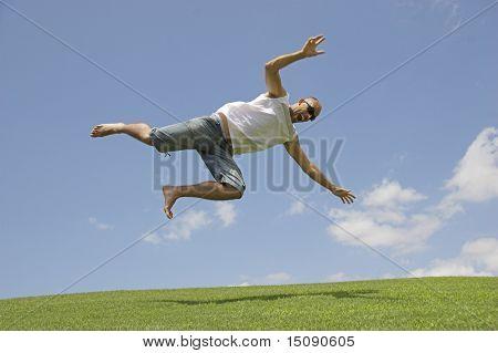 Man die vallen in het gras van een weide