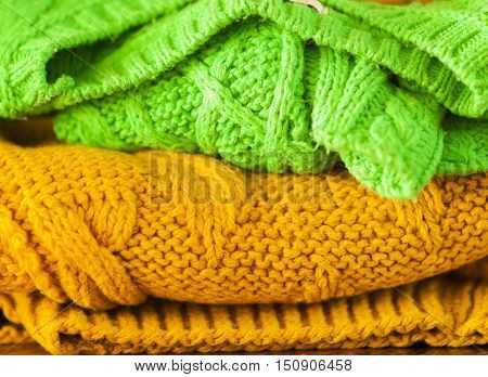 green and orange knitted woolen sweaters closeup