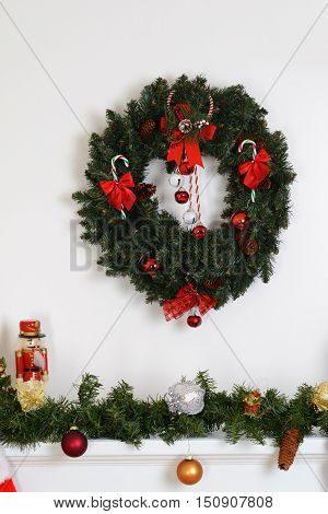 christmas wreath over fireplace mantel with green garland