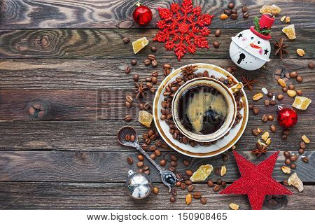 Rustic wooden background with cup of coffee and New Year decorations. White vintage dinnerware and spoon. Christmas beverage with ginger and anise. Top view place for text.