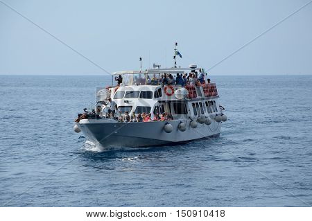 Riomaggiore Italy - September 4 2016: Passenger boat nearby Riomaggiore city in Liguria Italy. One of five Cinque Terre cities (unesco world heritage). Unidentified people visible.