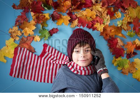 seven years old boy dreaming in autumn. Child in hat and scarf and maple leaves on blue background speaking on the smartphone