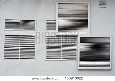 Many large and small ventilation grilles on the metal wall.