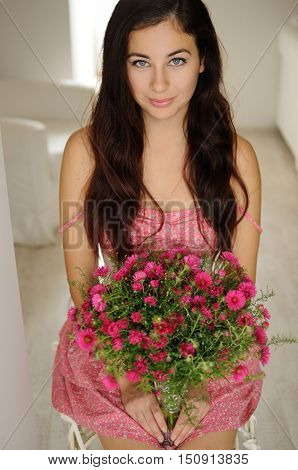 Pretty girl sitting with a bouquet of flowers in pink floral dress and white corset
