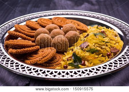 Plate full of indian festival food or diwali food or snacks like laddu, chivda, chakali or murukku, sev and shankar pale, sweet and salty snack food