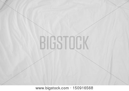 Top view of bedding sheets crease, white fabric texture soft focus