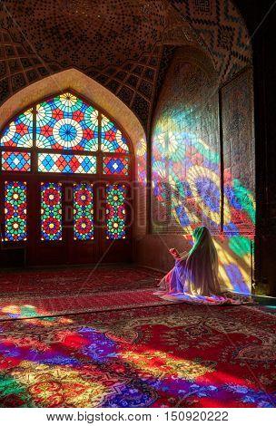 SHIRAZ, IRAN - March 01, 2016: Muslim womanin white clothes praying in Nasir Al-Mulk Mosque (Pink Mosque), Iran, Shiraz
