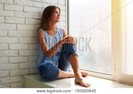 Charming romantic young girl looking out of the window wearing stylish casual outfit