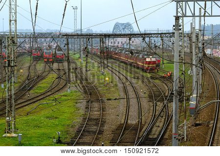 SAINT-PETERSBURG RUSSIA - Old locomotives RZD stand on railroad tracks of technical railway station - operational locomotive depot on autumn morning in fog. Workers in overalls serve rail journey. Transport infrastructure of Russian Railways St. Petersbur