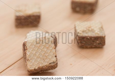Wafers with chocolate on wooden background .