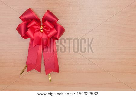 Red gift bow ribbon on wooden table.