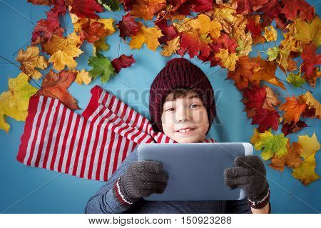 seven years old boy dreaming in autumn. Child in hat and scarf and maple leaves on blue background holding a tablet