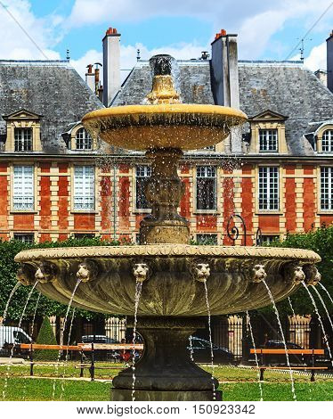 Historic fountain with lion heads in park of the famous Place des Vosges in Paris