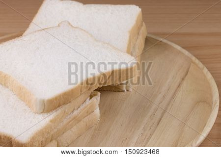 Whole wheat bread on wooden plate placed of wooden background.