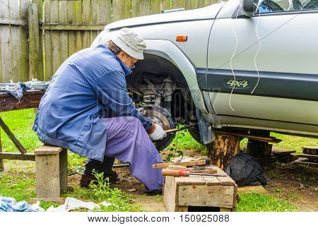 The mechanic is repairing the front suspension of the car at home. Car repair is a service station environment.