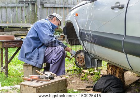 Senior mechanic repairing the front hub wheels. car repair at home.