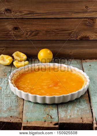 Lemon pie with fresh and squeezed lemon on wooden background with copyspace