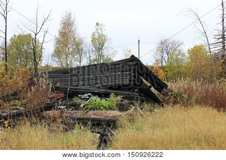 Destroyed burned out abandoned old house foundation ruins at the countryside village. Fire alarm notification system accident insurance protection concept.