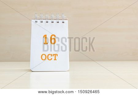 Closeup surface note book with orange 16 oct word in page on blurred brown wood desk and wood wall textured background with copy space under window light