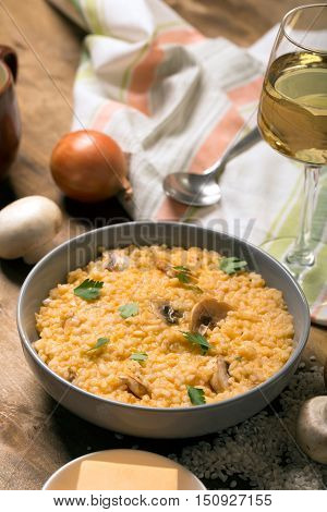 Risotto with mushrooms, fresh herbs and parmesan cheese. Wooden background