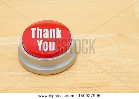 A Thank You red push button A red and silver push button on a wooden desk with text Thank You