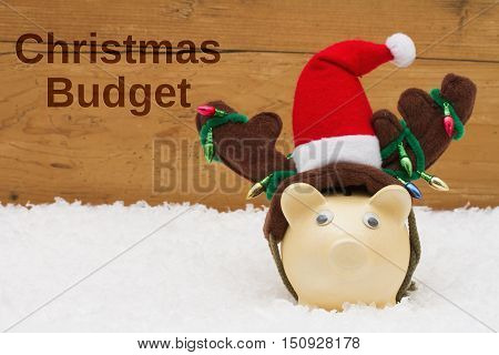 Having a Christmas Budget Piggy bank with Christmas hat on snow with a weathered wood background with text Christmas Budget