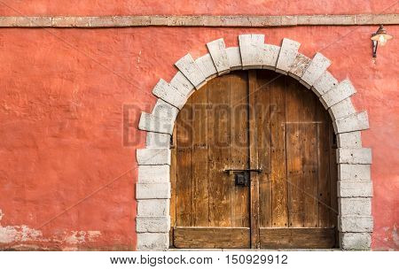 Wooden medieval door and orange wall - Medieval architecture background with a massive wooden door and an orange-pink aged wall with copy space on left