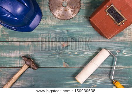 Construction concept. Roller hammer hard hat circular saw blade and welding mask on nice green wood background.